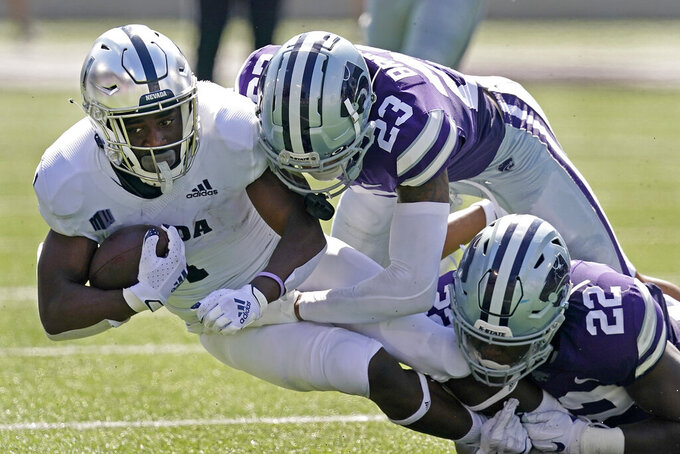 Nevada wide receiver Melquan Stovall (1) is tackled by Kansas State defensive back Julius Brents (23) and linebacker Daniel Green (22) during the first half of an NCAA college football game Saturday, Sept. 18, 2021, in Manhattan, Kan. (AP Photo/Charlie Riedel)