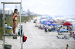 Kure Beach Ocean Rescue lifeguard Katy Kelly looks out from a stand at Kure Beach, N.C., Saturday, May 23, 2020. The town lifted the majority of beach restrictions related to the coronavirus on May 15. (Matt Born/The Star-News via AP)
