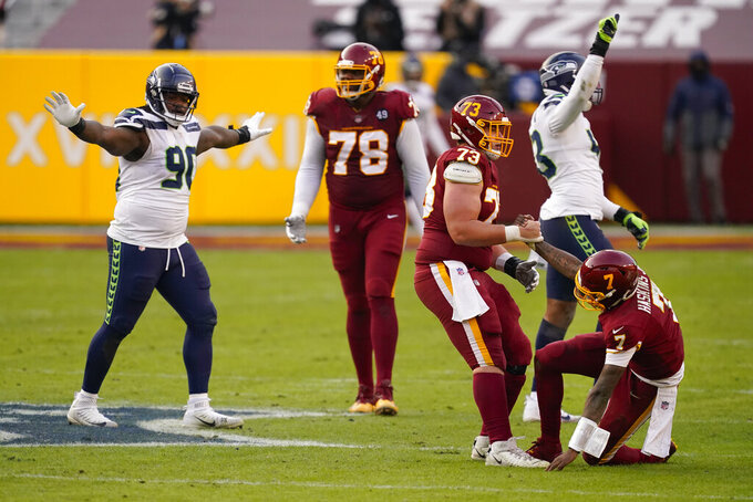 Washington Football Team quarterback Dwayne Haskins (7) is helped getting up by teammate Washington Football Team center Chase Roullier (73) as members of the Seattle Seahawks celebrate in the closing seconds of an NFL football game between, Sunday, Dec. 20, 2020, in Landover, Md. Seattle won 20-15. (AP Photo/Andrew Harnik)