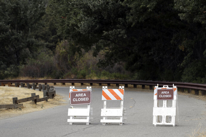 Signs indicate a road closure at the Malibu Creek State Park Thursday, Oct. 11, 2018, in Calabasas, Calif. Investigators will use ballistic testing to determine if a rifle carried by a burglary suspect was used in the killing of a camper at the California wilderness park. Authorities say 42-year-old Anthony Rauda had the gun and was dressed in black when he was arrested Wednesday after a search of a rugged canyon area near Malibu. (AP Photo/Marcio Jose Sanchez)