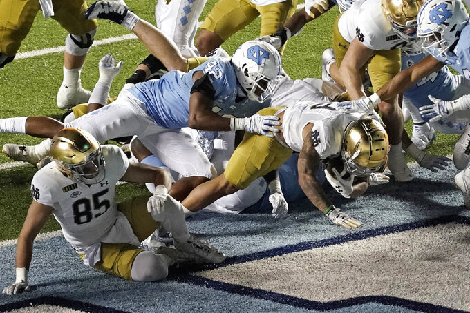 Notre Dame running back Kyren Williams scores a touchdown while North Carolina linebacker Tyrone Hopper (42) tries to make the stop during the second half of an NCAA college football game in Chapel Hill, N.C., Friday, Nov. 27, 2020. (AP Photo/Gerry Broome)