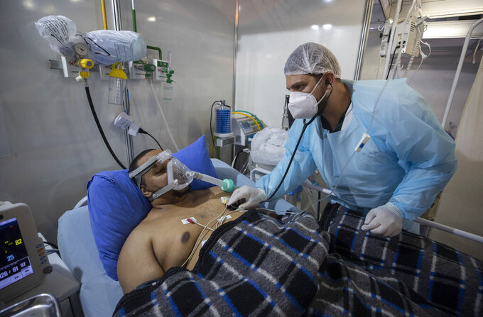 COVID-19 patient Everton Nascimento de Oliveira, 32, receives treatment at the emergency unit of a field hospital set up for COVID patients in Ribeirao Pires, greater Sao Paulo area, Brazil, Tuesday, April 13, 2021. (AP Photo/Andre Penner)