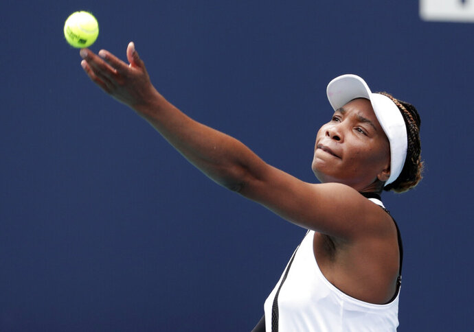 Venus Williams tosses the ball to serve to Dalila Jakupovic, of Slovenia, at the Miami Open tennis tournament, Thursday, March 21, 2019, in Miami Gardens, Fla. (AP Photo/Lynne Sladky)