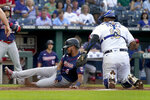 Minnesota Twins' Luis Arraez (2) beats the tag by Kansas City Royals catcher Salvador Perez (13) to score on a single by Trevor Larnach during the first inning of a baseball game Friday, July 2, 2021, in Kansas City, Mo. (AP Photo/Charlie Riedel)
