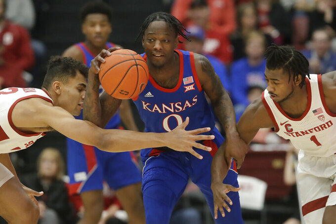 Kansas guard Marcus Garrett (0) dribbles between Stanford forward Oscar da Silva, left, and guard Daejon Davis during the first half of an NCAA college basketball game in Stanford, Calif., Sunday, Dec. 29, 2019. (AP Photo/Jeff Chiu)