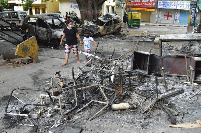 A woman and a child walks past the wreckage of vehicles and furniture burnt during violent protests in Bengaluru, India, Wednesday, Aug. 12, 2020. At least three people have died in the southern Indian city also known as Bangalore after hundreds of demonstrators clashed with the police overnight against a Facebook post considered offensive to Muslims, attacking a police station and setting fire to vehicles, police said Wednesday. (AP Photo)