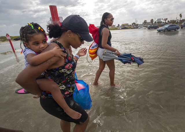 Stacey Young gives her daughter, Kylee Potts, a piggyback ride across the flooding Stewart Beach parking lot in Galveston, Texas on Saturday, Sept. 19, 2020. Tropical Storm Beta continues to move through the Gulf of Mexico and is expected to bring tidal surge and heavy rain to the area.  (Stuart Villanueva/The Galveston County Daily News via AP)