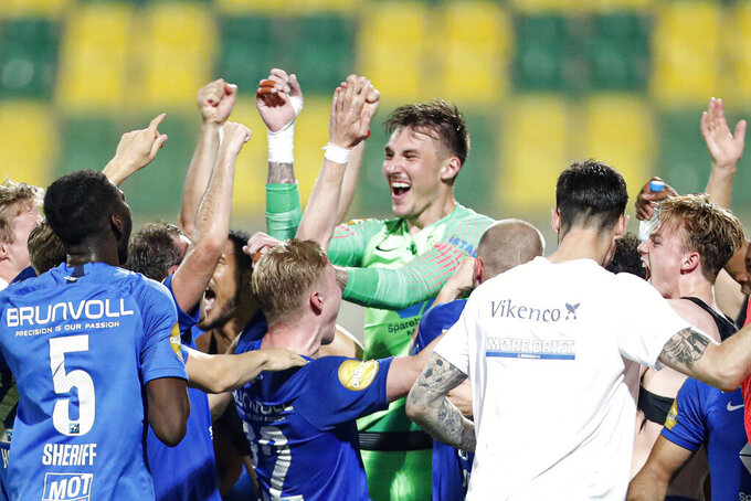 Molde's goalkeeper Andreas Linde, center, celebrates with teammates at the end the Champions League third qualifying round soccer match between between Molde and Quarabag FK at the AEK Arena in Larnaca, Cyprus, Wednesday, Sept. 16, 2020. (AP Photo/Petros Karadjias)