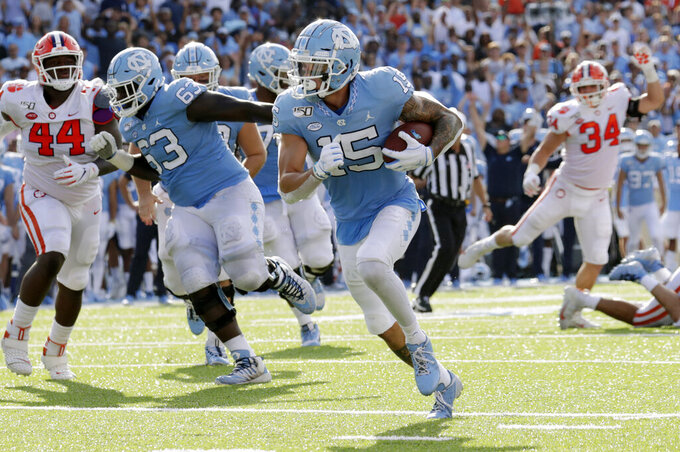 North Carolina's Beau Corrales (15) runs for a touchdown behind the block of Ed Montilus (63) while Clemson's Nyles Pinckney (44) looks on during the second quarter of an NCAA college football game in Chapel Hill, N.C., Saturday, Sept. 28, 2019. (AP Photo/Chris Seward)