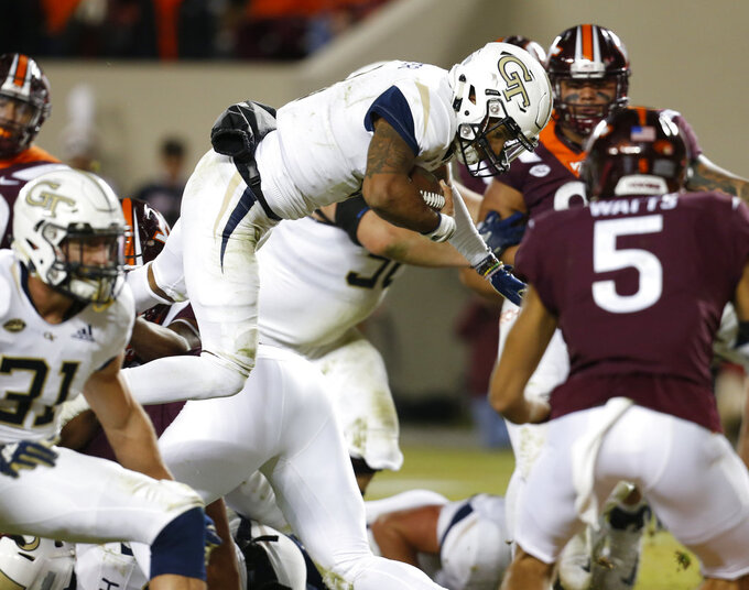 Georgia Tech quarterback Tobias Oliver (8) leaps over the pile to score against Virginia Tech during the first half of an NCAA college football game in Blacksburg, Va., Thursday, Oct. 25, 2018. (AP Photo/Steve Helber)