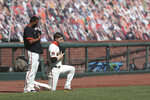 San Francisco Giants' Austin Slater, right, kneels next to teammate Wandy Peralta during the national anthem before a baseball game against the Colorado Rockies in San Francisco, Thursday, Sept. 24, 2020. (AP Photo/Jed Jacobsohn)