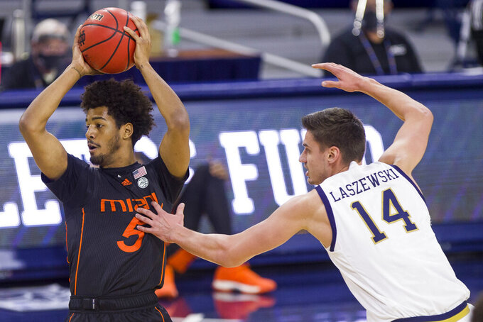 Miami's Harlond Beverly (5) is pressured by Notre Dame's Nate Laszewski (14) during the first half of an NCAA college basketball game Sunday, Feb. 14, 2021, in South Bend, Ind. (AP Photo/Robert Franklin)