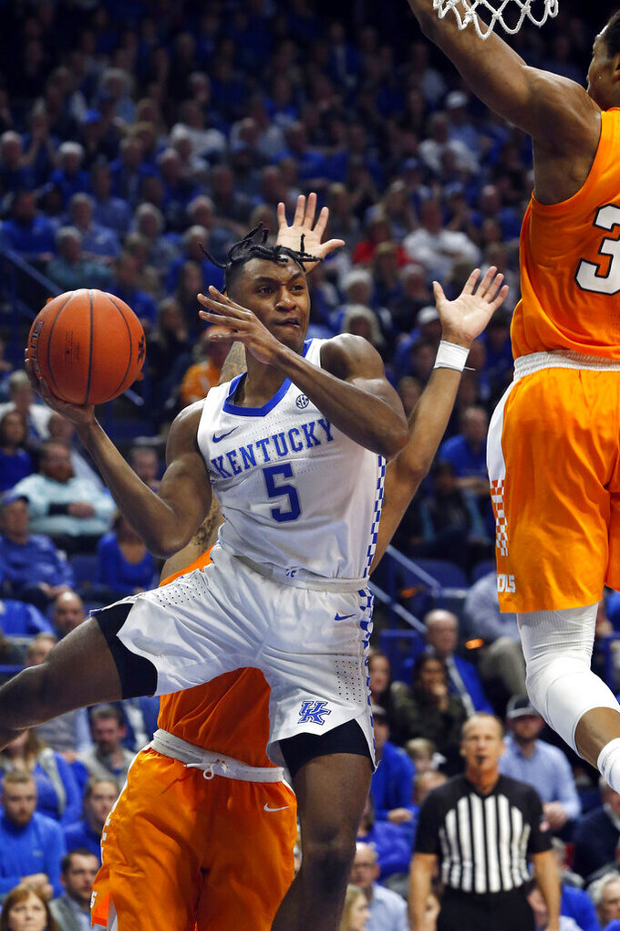 Kentucky's Immanuel Quickley (5) passes the ball around Tennessee's Yves Pons, right, during the second half of an NCAA college basketball game Tuesday, March 3, 2020, in Lexington, Ky. Tennessee won 81-73. (AP Photo/James Crisp)