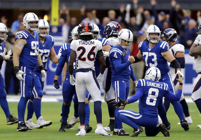 Indianapolis Colts kicker Adam Vinatieri (4) reacts with punter Rigoberto Sanchez (8) after making a winning field goal during the second half of an NFL football game against the Denver Broncos, Sunday, Oct. 27, 2019, in Indianapolis. (AP Photo/Darron Cummings)