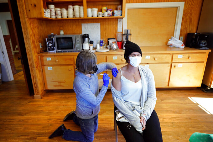 Nurse Sharon Daley, administers a COVID-19 vaccination to Hollie Stanley in a makeshift clinic in the kitchen of a community center, Friday, March 19, 2021, on Great Cranberry Island, Maine. (AP Photo/Robert F. Bukaty)