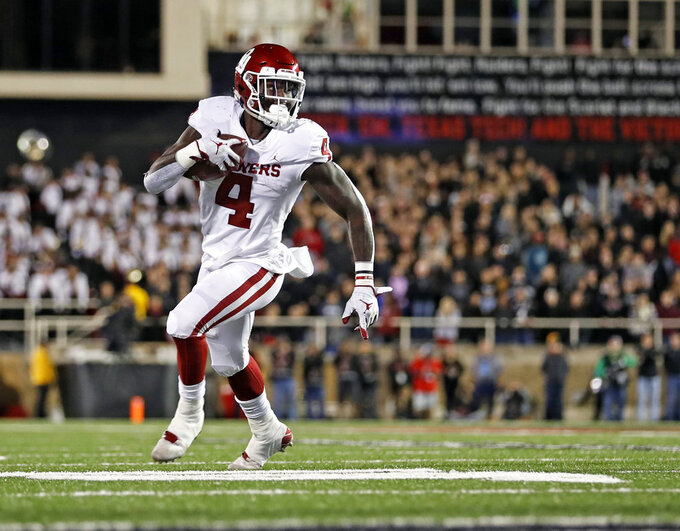 Oklahoma's Trey Sermon (4) runs downfield with the ball during the first half of an NCAA college football game against Texas Tech, Saturday, Nov. 3, 2018, in Lubbock, Texas. (AP Photo/Brad Tollefson)