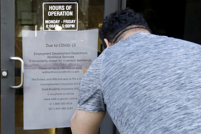 FILE - In this March 26, 2020 file photo a man takes a photo of a sign advising that the Employment Development Department is closed due to coronavirus concerns, in San Francisco. A review of California's unemployment agency has found its productivity level declined despite hiring hundreds of new workers. The Employment Development Department has been overwhelmed by millions of claims for unemployment benefits during the coronavirus pandemic. (AP Photo/Jeff Chiu, File)