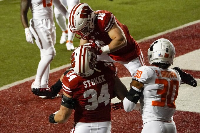 Wisconsin's Mason Stokke celebrates his touchdown catch with Jack Dunn (16) during the first half of an NCAA college football game against Illinois Friday, Oct. 23, 2020, in Madison, Wis. (AP Photo/Morry Gash)