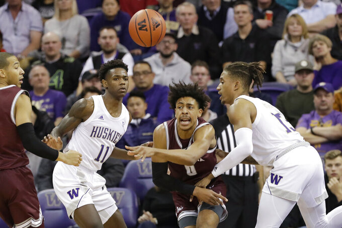 Montana's Kyle Owens (0) gets a pass off between Washington's Nahziah Carter (11) and Hameir Wright (13) during the second half of an NCAA college basketball game Friday, Nov. 22, 2019, in Seattle. (AP Photo/Elaine Thompson)
