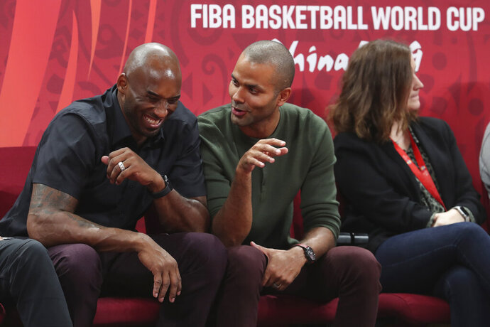 Former NBA players Kobe Bryant, left, and Tony Parker talk during the first-place match between Spain and Argentina in the FIBA Basketball World Cup at the Cadillac Arena in Beijing, Sunday, Sept. 15, 2019. (AP Photo/Ng Han Guan)