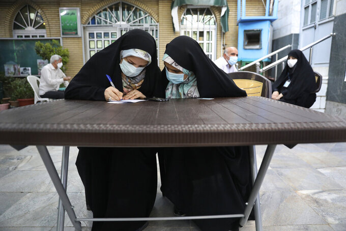 A voter fills out her ballot papers at a polling station during the presidential elections in Tehran, Iran, Friday, June 18, 2021. Iranians voted Friday in a presidential election dominated by a hard-line protege of Supreme Leader Ayatollah Ali Khamenei after authorities disqualified nearly all of his strongest competition, leading to what appeared to be a low turnout fueled by apathy and calls for a boycott. (AP Photo/Vahid Salemi)