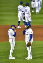 Toronto Blue Jays third baseman Cavan Biggio, left, and first baseman Vladimir Guerrero Jr. celebrate a win over the New York Yankees in a baseball game in Buffalo, N.Y., Monday, Sept. 21, 2020. (AP Photo/Adrian Kraus)