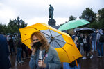 People with umbrellas gather during a rally to cancel the results of voting on amendments to the Constitution in Pushkin square with the statue of Alexander Pushkin in the background in Moscow, Russia, Wednesday, July 15, 2020. Earlier this month a group of opposition activists called for a protest against the constitutional reform that allows Russian President Vladimir Putin to stay in power until 2036. (AP Photo/Alexander Zemlianichenko)