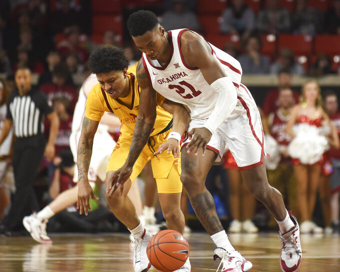 Oklahoma forward Kristian Doolittle (21) tries to steal the ball from Iowa State Prestiss Nixon (11) during the second half of an NCAA college basketball game in Norman, Okla., Wednesday, Feb. 12, 2020. (AP Photo/Kyle Phillips)