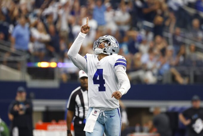 Dallas Cowboys quarterback Dak Prescott (4) celebrates after throwing a touchdown pass to tight end Blake Jarwin in the first half of a NFL football game against the Carolina Panthers in Arlington, Texas, Sunday, Oct. 3, 2021. (AP Photo/Ron Jenkins)