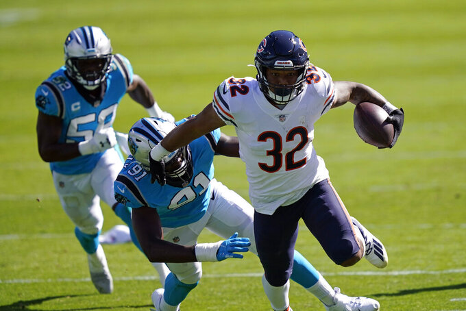 Chicago Bears running back David Montgomery (32) breaks a tackle by Carolina Panthers defensive end Stephen Weatherly (91) during the first half of an NFL football game in Charlotte, N.C., Sunday, Oct. 18, 2020. (AP Photo/Brian Blanco)