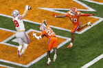 Ohio State tight end Jeremy Ruckert, left, scores in front of Clemson cornerback Andrew Booth Jr. and safety Joseph Charleston during the first half of the Sugar Bowl NCAA college football game Friday, Jan. 1, 2021, in New Orleans. (AP Photo/Butch Dill)