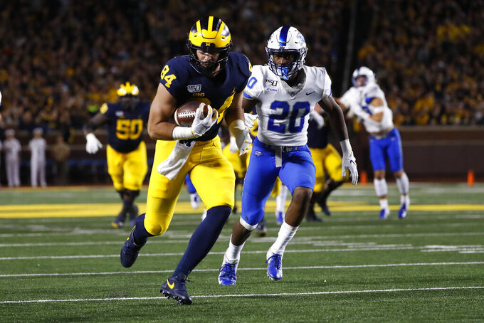 Michigan tight end Sean McKeon (84) runs with a 28-yard touchdown reception during the first half of an NCAA college football game against Middle Tennessee in Ann Arbor, Mich., Saturday, Aug. 31, 2019. Middle Tennessee's DQ Thomas is at right. (AP Photo/Paul Sancya)