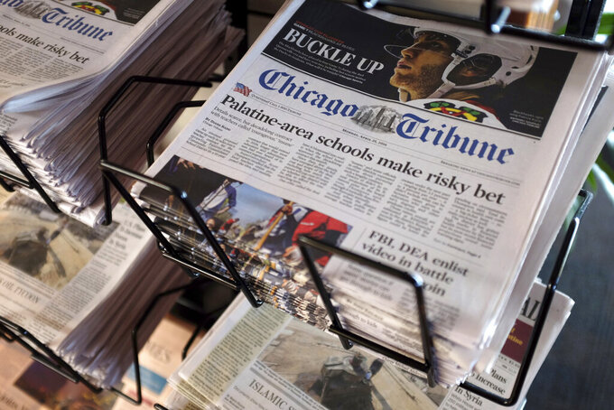 FILE - In this Monday, April 25, 2016, file photo, Chicago Tribune and other newspapers are displayed at Chicago's O'Hare International Airport.  Shareholders of Tribune Publishing, one of the country's largest newspaper chains, will vote Friday, May 21, 2021, on whether to be acquired by a hedge fund that already owns one-third of the company and favors aggressive cost-cutting to boost profits. (AP Photo/Kiichiro Sato, File)