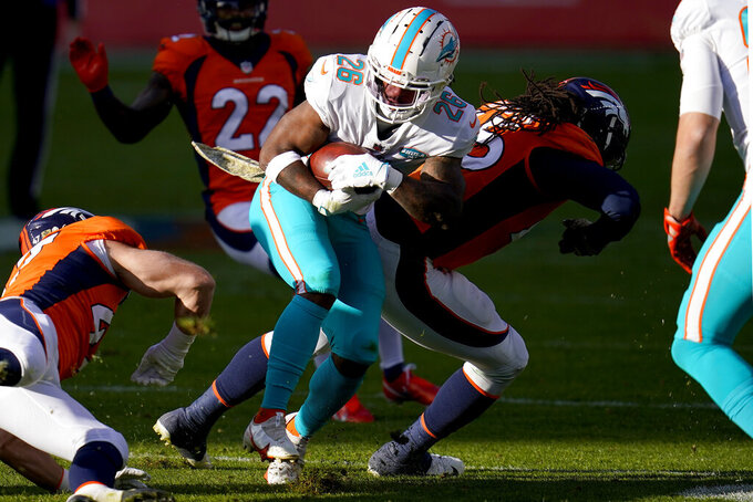 Miami Dolphins running back Salvon Ahmed (26) is hit by Denver Broncos inside linebacker A.J. Johnson, right, during the first half of an NFL football game, Sunday, Nov. 22, 2020, in Denver. (AP Photo/David Zalubowski)