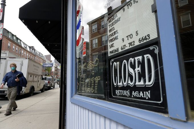 FILE - In this May 12, 2020 file photo, a pedestrian passes a closed barbershop during the coronavirus pandemic, in the North End neighborhood of Boston. Many small-business owners took on debt to weather the coronavirus pandemic, which forced lockdowns and decimated revenues for large sectors of the economy. Now, those business owners are faced with repaying this debt and rebuilding their companies.  (AP Photo/Steven Senne, File)