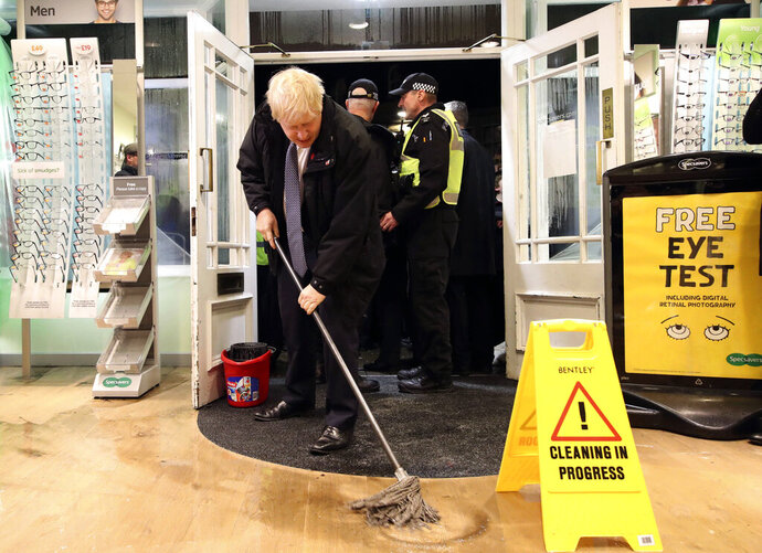 Britain's Prime Minister Boris Johnson visits an optician shop after flooding, in Matlock, north England, Friday Nov. 8, 2019. A woman died after being swept away by surging waters as torrential rain drenched parts of north and central England, swelling rivers, forcing evacuations and disrupting travel for a second day Friday. (Danny Lawson/PA via AP)