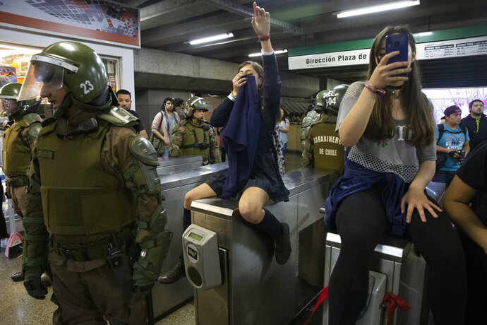 FILE - In this Oct. 18, 2019 file photo, police stand next to students blocking the turnstile to the subway protesting against the rising cost of subway and bus fare, in Santiago. (AP Photo/Esteban Felix, File)