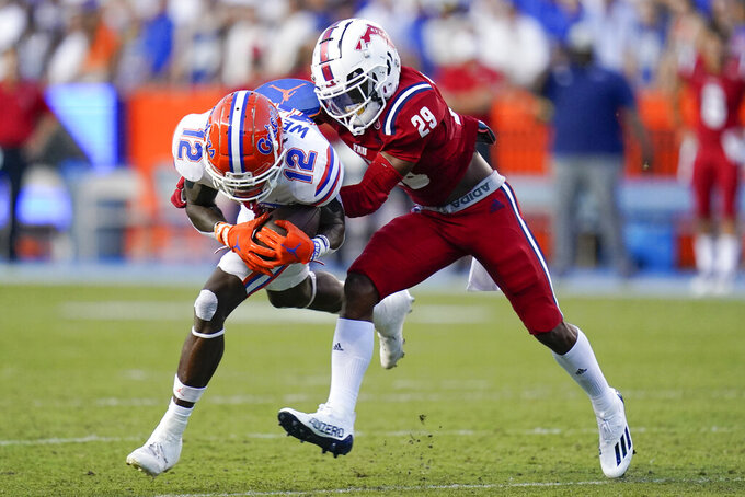 Florida wide receiver Rick Wells (12) is stopped by Florida Atlantic cornerback Korel Smith (29) after a reception during the first half of an NCAA college football game Saturday, Sept. 4, 2021, in Gainesville, Fla. (AP Photo/John Raoux)