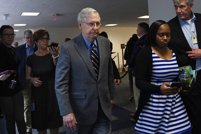 Senate Majority Leader Mitch McConnell of Ky., is followed by reporters and staff as he leaves a meeting on Capitol Hill in Washington, Friday, March 20, 2020, to work on an economic package to deal with the coronavirus. (AP Photo/Susan Walsh)