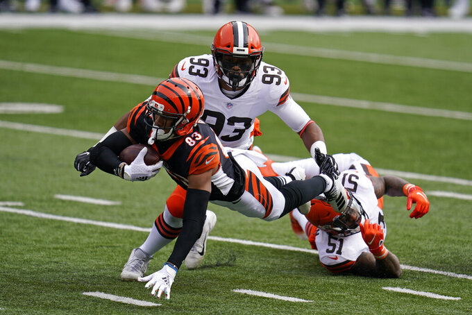 Cincinnati Bengals' Tyler Boyd (83) is tackled by Cleveland Browns' Mack Wilson (51) and B.J. Goodson (93) during the first half of an NFL football game, Sunday, Oct. 25, 2020, in Cincinnati. (AP Photo/Michael Conroy)