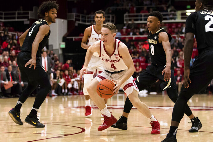 Stanford guard Isaac White (4) dribbles as Colorado guard Shane Gatling (0) and others defend during the first half of an NCAA college basketball game in Stanford, Calif., Saturday, Jan. 26, 2019. (AP Photo/John Hefti)