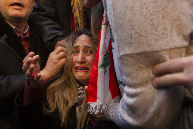 An injured woman cries out as she is assisted during an anti-government protest outside of the Beirut municipality in Lebanon, Friday, Jan. 10, 2010. Scuffles broke out between anti—government protesters calling for the ouster of the city's mayor and the governor of the province, and supporters of outgoing Prime Minister Saad Hariri, who handpicked them. (AP Photo/Maya Alleruzzo)
