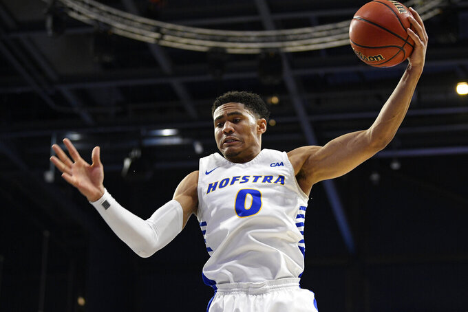 Hofstra guard Tareq Coburn grabs a rebound during the first half of the team's NCAA college basketball game against Northeastern for the championship of the Colonial Athletic Association men's tournament Tuesday, March 10, 2020, in Washington. (AP Photo/Nick Wass)