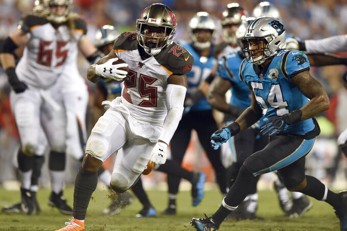 Tampa Bay Buccaneers running back Peyton Barber (25) runs for a touchdown while Carolina Panthers outside linebacker Shaq Thompson (54) looks to tackle during the second half of an NFL football game in Charlotte, N.C., Thursday, Sept. 12, 2019. (AP Photo/Mike McCarn)