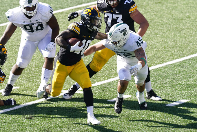 Iowa running back Mekhi Sargent (10) runs from Michigan State linebacker Noah Harvey (45) during the first half of an NCAA college football game, Saturday, Nov. 7, 2020, in Iowa City, Iowa. (AP Photo/Charlie Neibergall)