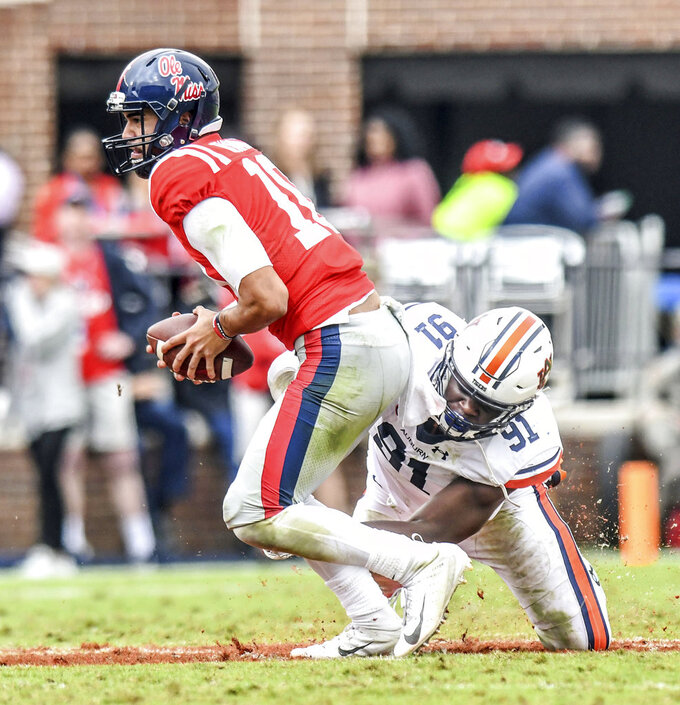 Mississippi quarterback Jordan Ta'amu (10) is sacked by Auburn defensive lineman Nick Coe (91) during an NCAA college football game at Vaught-Hemingway Stadium in Oxford, Miss., Saturday, Oct. 20, 2018. (Bruce Newman/The Oxford Eagle via AP)