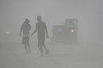 Residents walk in a cloud of ash as Taal Volcano continues to spew ash on Monday Jan. 13, 2020, in Tagaytay, Cavite province, south of Manila, Philippines. Red-hot lava gushed out of the Philippine volcano Monday after a sudden eruption of ash and steam that forced villagers to flee en masse and shut down Manila's international airport, offices and schools.(AP Photo/Aaron Favila)