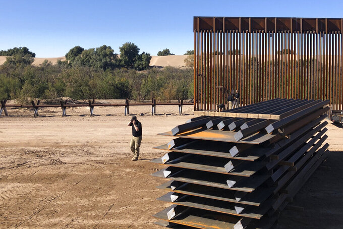 A man passes new border wall sections, right, as they replace the old fencing, left, Friday, Jan. 10, 2020, near Yuma, Arizona. Top Trump administration officials will visit South Texas five days before Election Day to announce they have completed 400 miles of U.S.-Mexico border wall, attempting to show progress on perhaps the president's best-known campaign promise four years ago. But most of the wall went up in areas that already had smaller barriers. (AP Photo/Elliot Spagat)