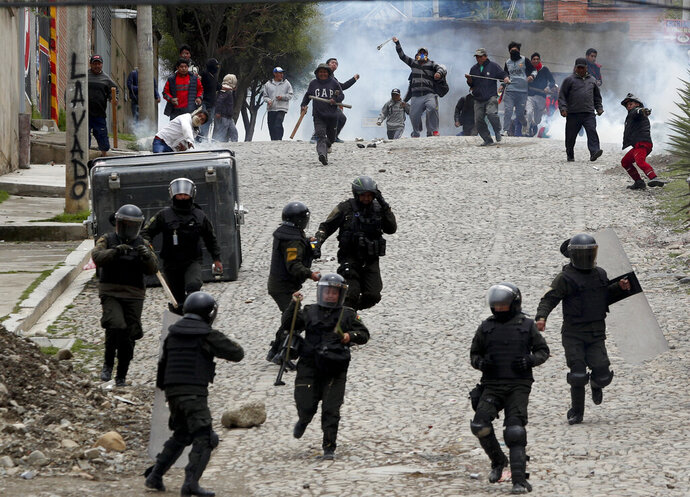 Supporters of former President Evo Morales clash with police in La Paz, Bolivia, Monday, Nov. 11, 2019. Morales' Nov. 10 resignation, under mounting pressure from the military and the public after his re-election victory triggered weeks of fraud allegations and deadly demonstrations, leaves a power vacuum and a country torn by protests against and for his government. (AP Photo/Juan Karita)