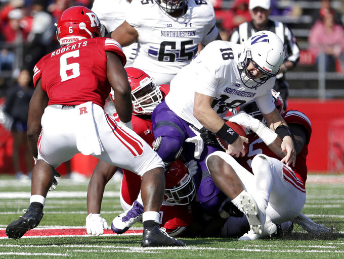 Northwestern quarterback Clayton Thorson, center, is stripped of the football by Rutgers linebacker Trevor Morris, right, during the second half of an NCAA college football game, Saturday, Oct. 20, 2018, in Piscataway, N.J. Rutgers recovered the fumble on the play. Northwestern won 18-15. (AP Photo/Julio Cortez)